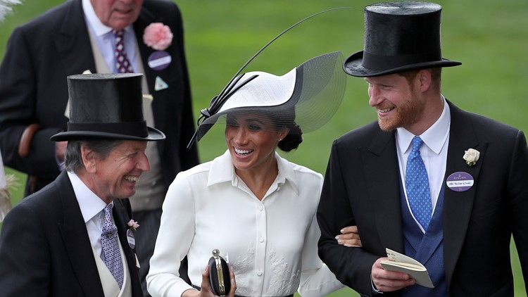 Britain's Prince Harry, Duke of Sussex, and his wife Britain's Meghan, Duchess of Sussex react as they talk with the Queen's Bloodstock and Racing Advisor, John Warren on day one of the Royal Ascot horse racing meet.