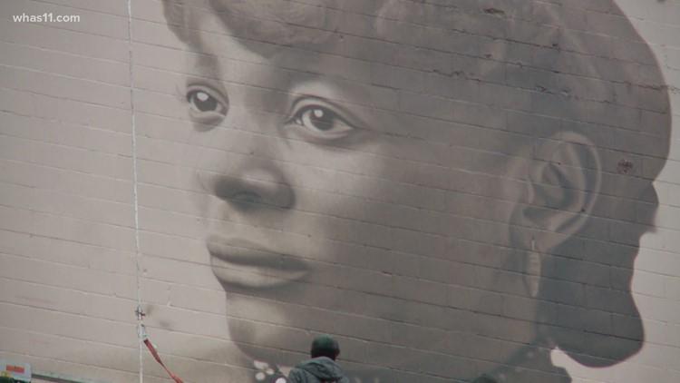 Artists working on mural of Henrietta Helm in downtown Louisville